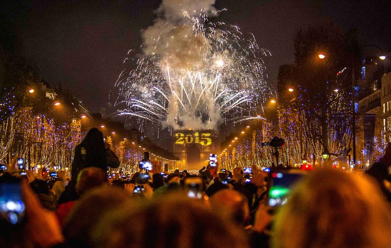 People watch the fireworks over the Arc de Triomphe as they celebrate the New Year's Eve on the Champs Elysees avenue in Paris, France, Dec. 31, 2014. (Xinhua/Chen ...
