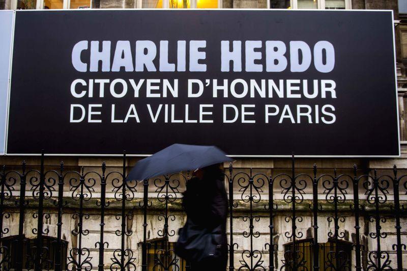 A pedestrian walks past an advertisement of Charlie Hebdo in Paris, France, on Jan. 9, 2015. Paris on Friday made the satirical magazine Charlie Hebdo an ...