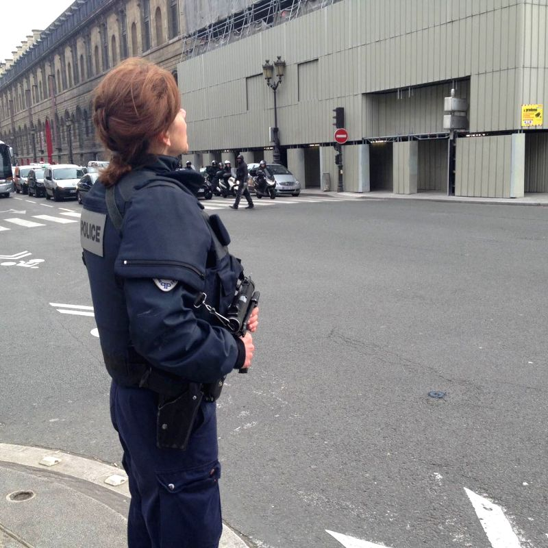 A policewoman stands guard near the Louvre Museum in Paris, France, Jan. 7, 2015. The office of Paris Prosecutor of the Republic confirmed at least 12 people were ...