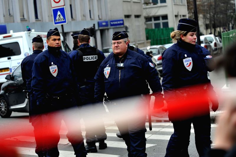 French police officers stand guard near the Paris office of Charlie Hebdo in Paris, France, Jan. 7, 2015. The office of Paris Prosecutor of the Republic confirmed at ..