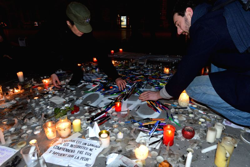 Local residents mourn for the people killed in the attack in Paris, France, on Jan. 7, 2015. At least 12 people were killed when two masked and armed men on Wednesday .