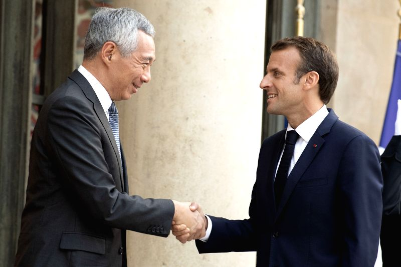 PARIS, July 14, 2018 - French President Emmanuel Macron (R) shakes hands with visiting Singaporean Prime Minister Lee Hsien Loong at the Elysee Palace in Paris, France, on July 13, 2018. - Lee Hsien Loong