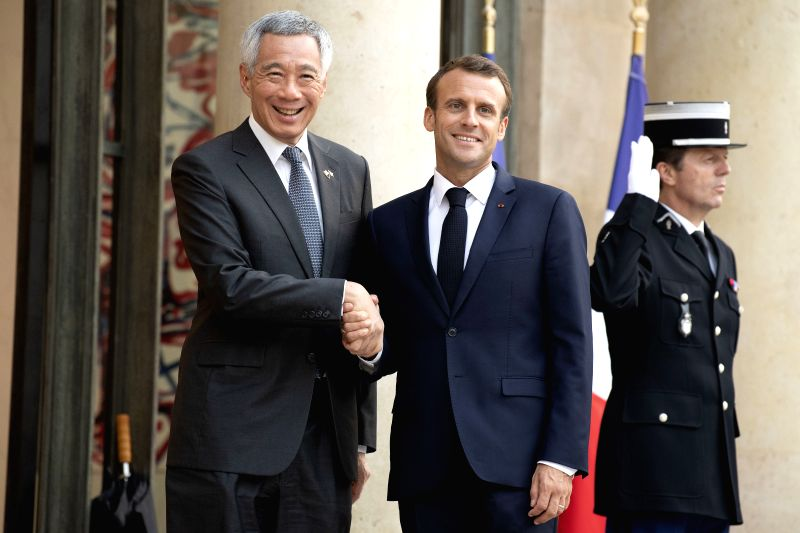 PARIS, July 14, 2018 - French President Emmanuel Macron (C) shakes hands with visiting Singaporean Prime Minister Lee Hsien Loong (L) at the Elysee Palace in Paris, France, on July 13, 2018. - Lee Hsien Loong