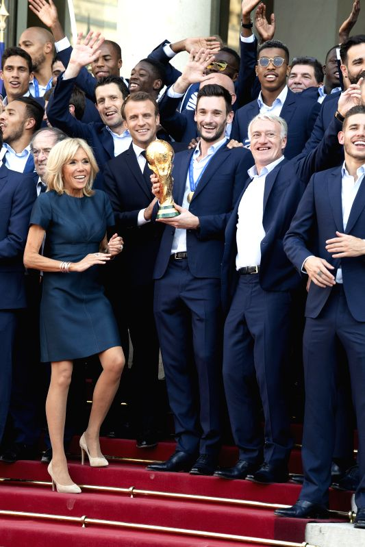 PARIS, July 17, 2018 - French President Emmanuel Macron (2nd L, front) and his wife Brigitte Macron (1st L, front) pose for photos with the French football team members at the Elysee Palace in Paris, ...