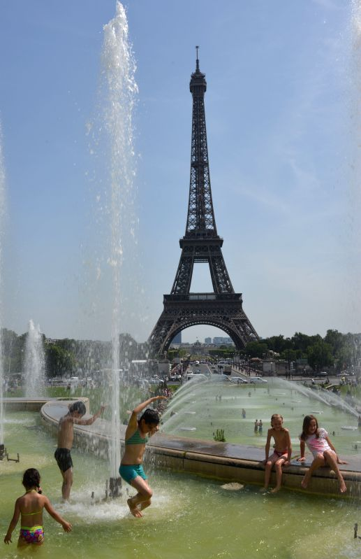 People cool themselves in a fountain near Eiffel Tower in Paris, France, July 18, 2014.