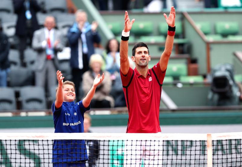 PARIS, June 1, 2016 - Novak Djokovic (R) of Serbia greets the audience with a ball boy after the men's singles fourth round match with Roberto Bautista Agut of Spain on day 11 of 2016 French Open ...