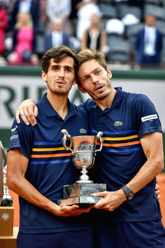 PARIS, June 10, 2018 - Pierre-Hugues Herbert (L) and Nicolas Mahut of France react during the awarding ceremony for men's doubles at the French Open Tennis Tournament 2018 in Paris, France on June 9, ...