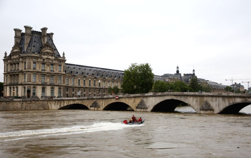 PARIS, June 3, 2016 - A police boat patrols on the Seine river in front of Louvre museum in Paris, France, June 3, 2016. Due to heavy rainfall across French cities, flood waters have reached alarming ...