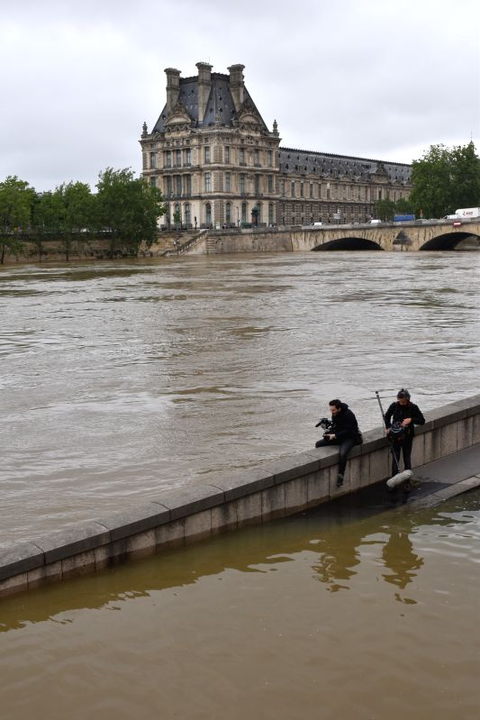 PARIS, June 3, 2016 - Two photographers take photos of Le Louvre Museum on the other side of Seine River in Paris, France, June 3, 2016. On high risks of floods, Le Louvre Museum closed its doors ...