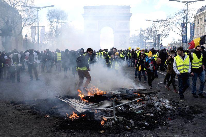 "PARIS, March 16, 2019 (Xinhua) -- ""Yellow Vest"" protesters burn barriers on the Champs-Elysees Avenue in Paris, France, on March 16, 2019. French police arrested more than 200 people on Saturday after violence broke out in Paris in a fresh protest of"