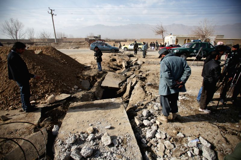 Afghan policemen inspect the site of blast in Parwan province, Afganistan, Dec. 13, 2014. A bomb attack targeted a NATO forces ' military convoy in eastern Afghanistan's Parwan province ...