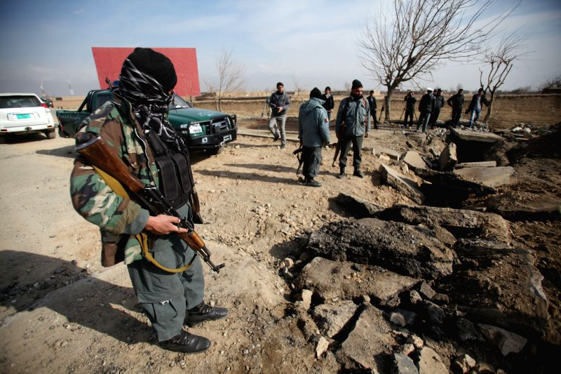 Afghan policemen keep watch at the site of blast in Parwan province, Afganistan, Dec. 13, 2014. A bomb attack targeted a NATO forces ' military convoy in eastern Afghanistan's Parwan province