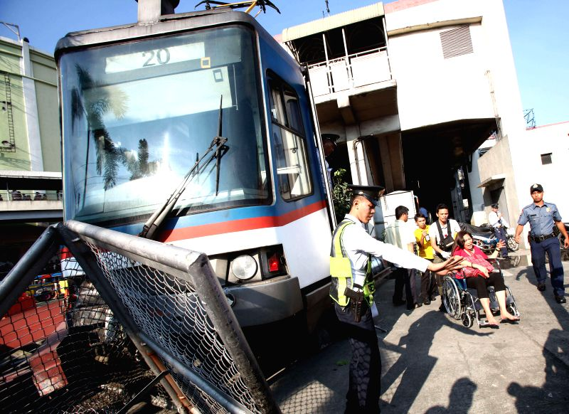 An injured passenger is carried on a wheelchair away from a derailed train coach in Pasay City, the Philippines, on Aug. 13, 2014. Around 20 passengers were ...