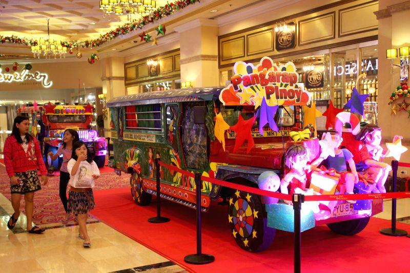People walk past a colorful jeepney during the Jeepney Design Challenge inside a mall in Pasay City, the Philippines, Dec. 22, 2014. The Jeepney Design Challenge