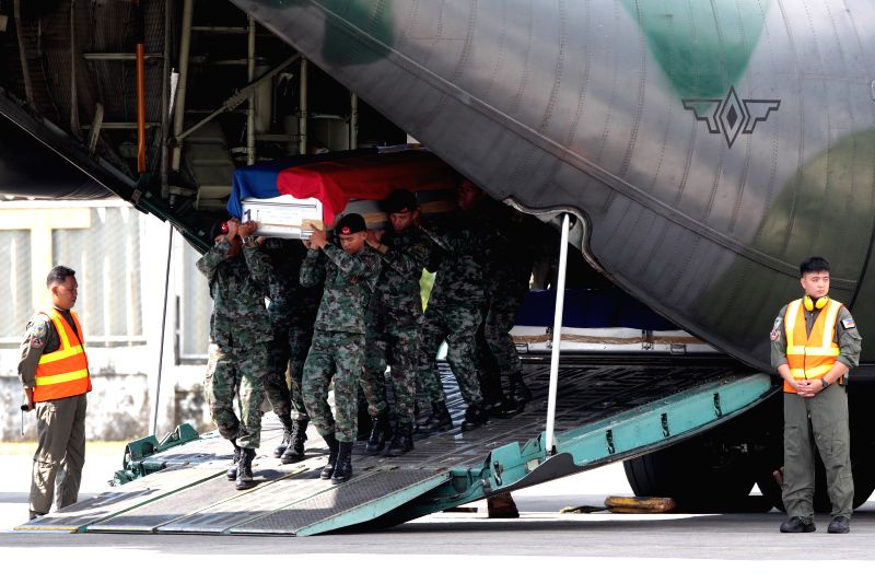 Members of the Philippine National Police Special Action Force (PNP-SAF) carry the casket of their fallen comrades at the Villamor Air Base in Pasay City, the ...