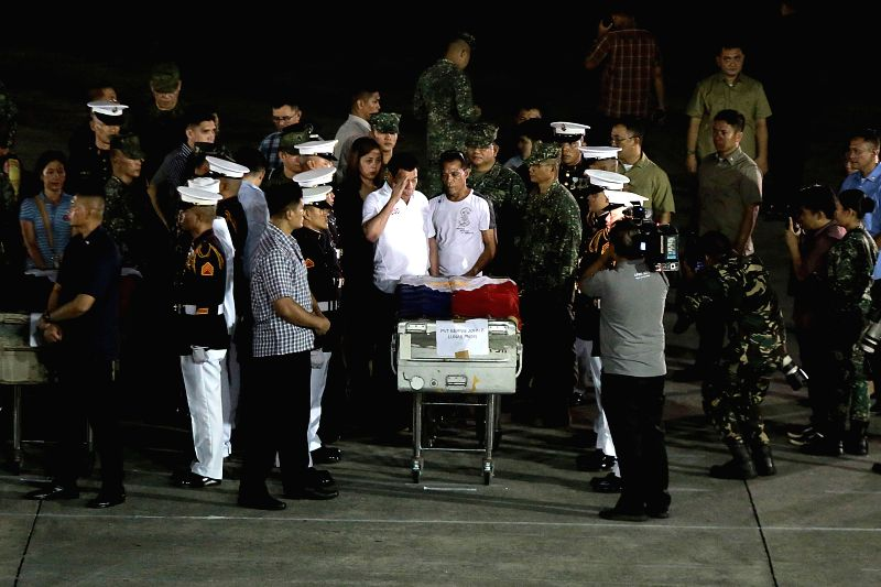 PASAY CITY, June 11, 2017 - Philippine President Rodrigo Duterte (C) salutes beside a relative of a fallen soldier during the battle of Marawi inside Villamor Air Base in Pasay City, the Philippines, ...