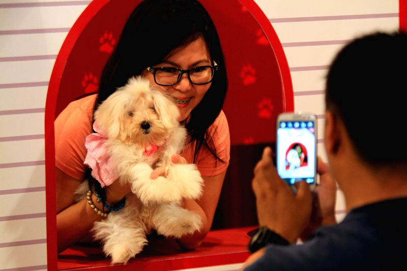 A woman holds her dog for a photo during the Dog and Cat Expo in Pasay City, the Philippines, June 29, 2014. The annual Dog and Cat Expo showcases various ...