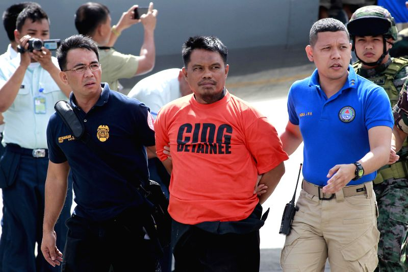 Mohammad Ali Tambako (C), founder of Justice Islamic Movement, a breakaway of Bangsamoro Islamic Freedom Fighters, is escorted in Pasay City, the Philippines, ...