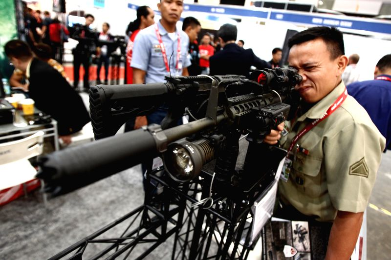 A member of the Philippine Army looks at a rifle during the Asian Defence and Security (ADAS) Exhibition 2014 in Pasay City, the Philippines, on July 17, 2014. More ..