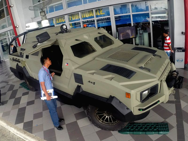 A member of the Philippine Navy looks at the Coastal Riverine Off-Road Craft during the Asian Defence and Security (ADAS) Exhibition 2014 in Pasay City, the ...