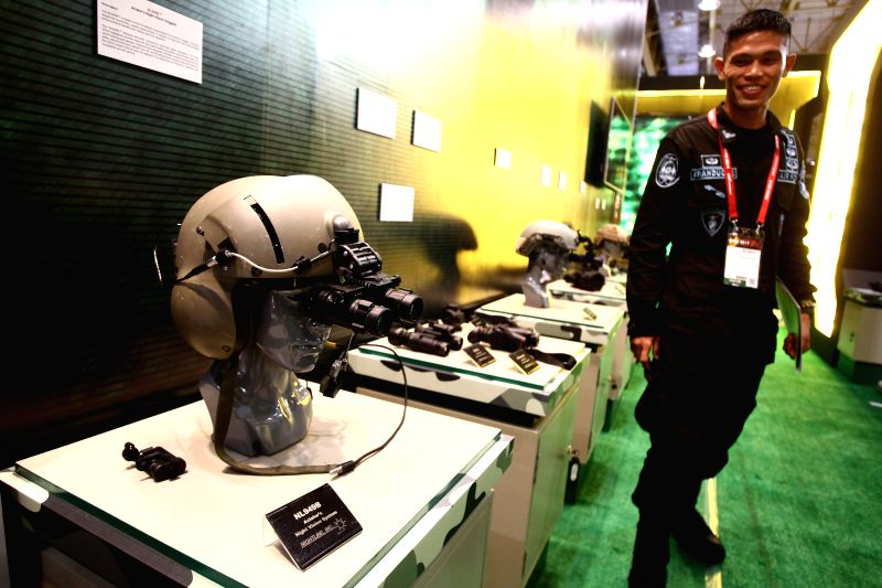 A member of the Philippine Air Force looks at a night vision system for aviators during the Asian Defence and Security (ADAS) Exhibition 2014 in Pasay City, the ...