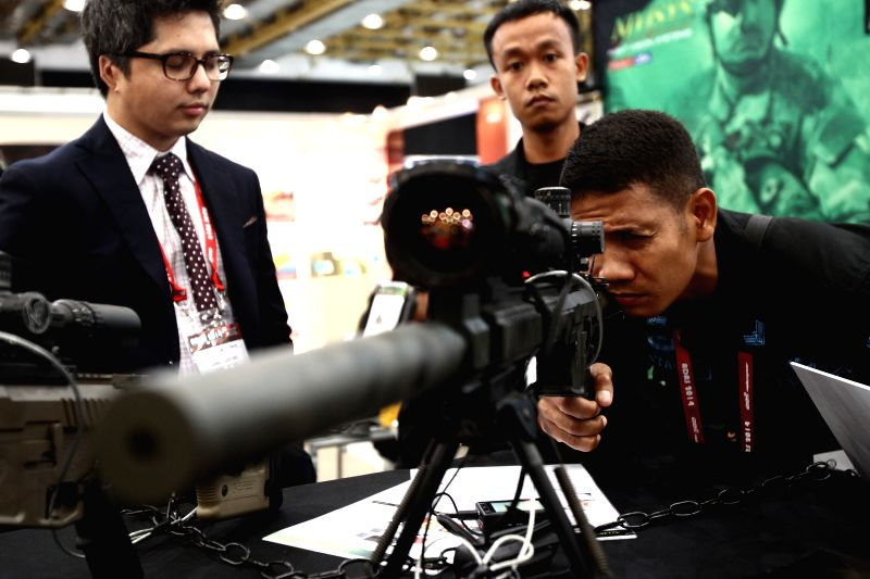 A member of the Philippine Air Force looks at a sniper rifle during the Asian Defence and Security (ADAS) Exhibition 2014 in Pasay City, the Philippines, on July 17, .
