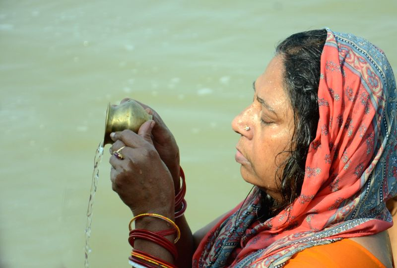 A woman performs rituals in the Ganga river on Makar Sankranti in Patna, on Jan 14, 2015.