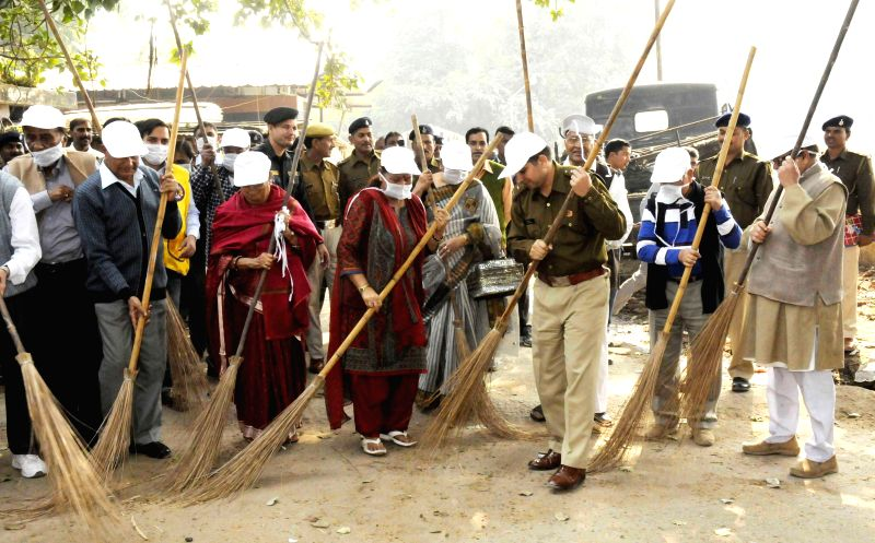 Activists and police officers participate in Swachha Bharat Abhiyan in Patna, on Nov 22, 2014.