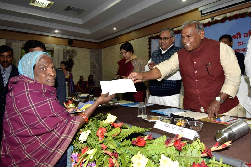 Bihar Chief Minister Jitan Ram Majhi handsover a cheque to a beneficiary of social security pension scheme during a programme in Patna, on Feb 18, 2015. - Jitan Ram Majhi