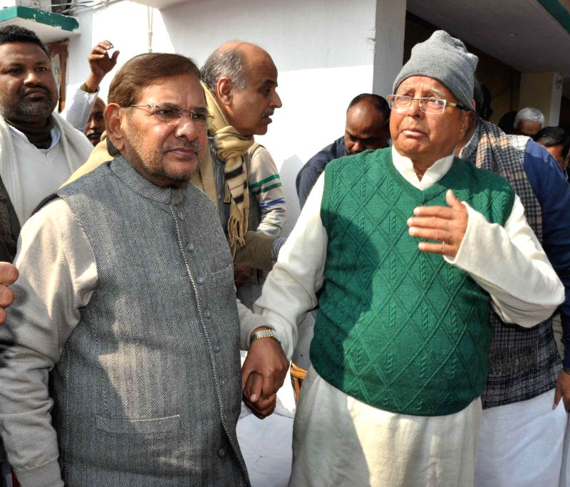 JD(U) chief Sharad Yadav with RJD supremo Lalu Prasad Yadav during a feast organised on Makar Sankranti at the latter's residence in Patna, on Jan 14, 2015. - Sharad Yadav and Lalu Prasad Yadav