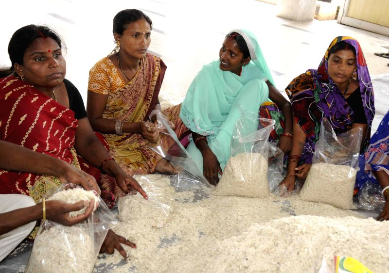 People make food packets of flattened rice for the Nepal quake victims in Patna, on April 27, 2015.