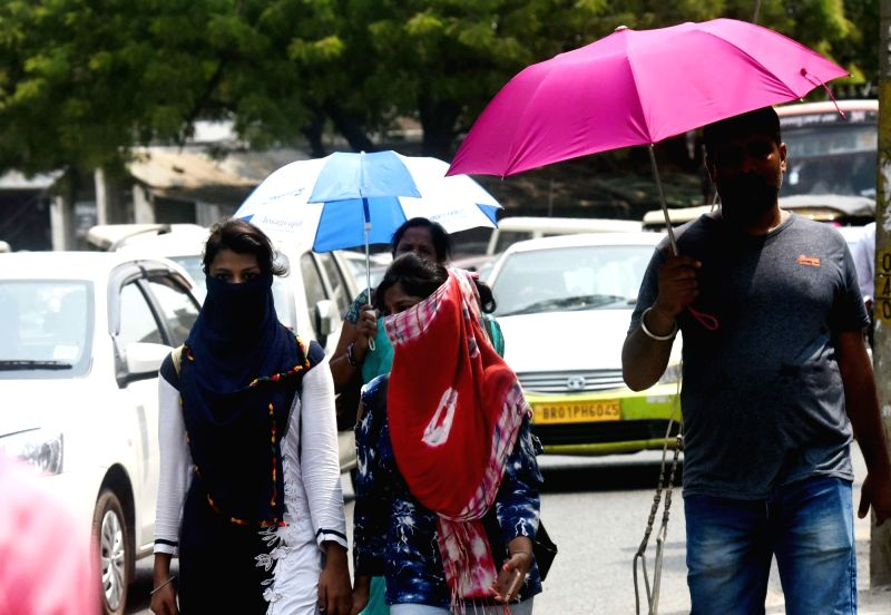Patna: People shield themselves from the scorching sun as heatwave conditions continue to prevail in Patna, on June 10, 2019.