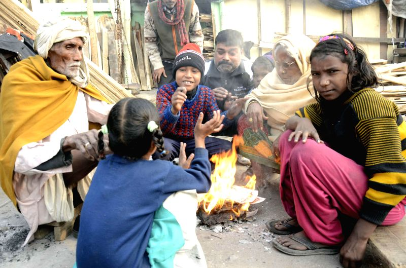 People warm themselves around a fire in Patna on Dec 21, 2014.
