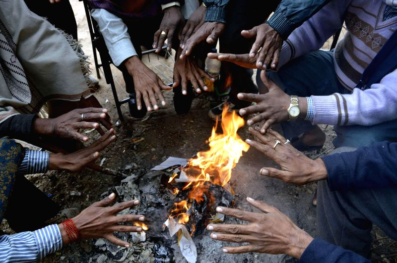 People warm themselves around a fire in Patna on Dec 23, 2014.