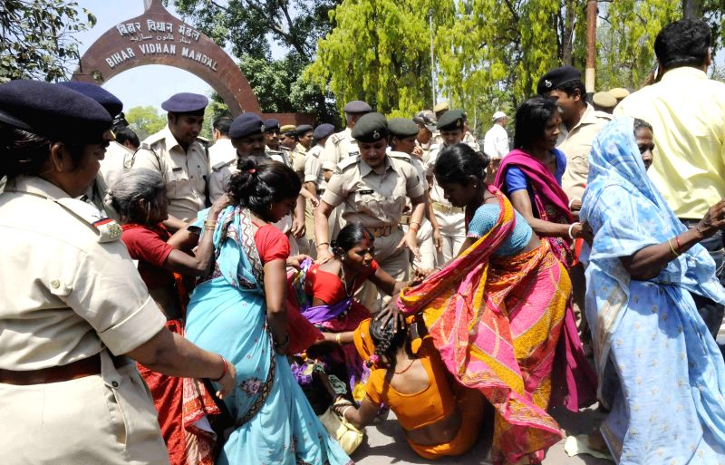 Police take away the activists of Bihar Navnirman Abhiyan stage a demonstration at Bihar Assembly in Patna on April 9, 2015.