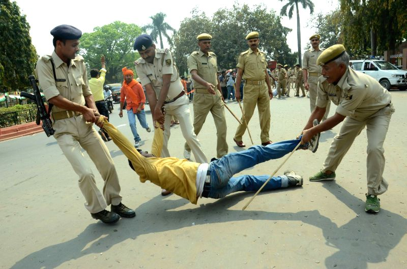 Policemen take away ABVP activists  staging a demonstration near state assembly in Patna, on March 26, 2015.