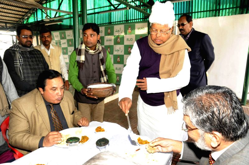RJD supremo Lalu Yadav serves food during Makar Sankranti feast organised at his residence in Patna, on Jan 15, 2015. - Lalu Yadav