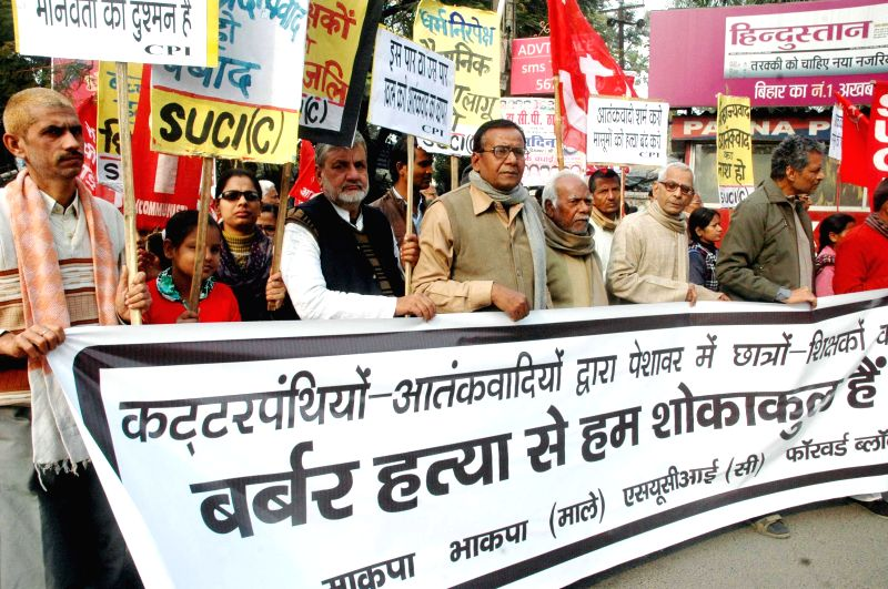 SUCI activists stage a demonstration to condemn the recent attack on a Peshawar school that left 148 dead, mostly children in Patna, on Dec 20, 2014.