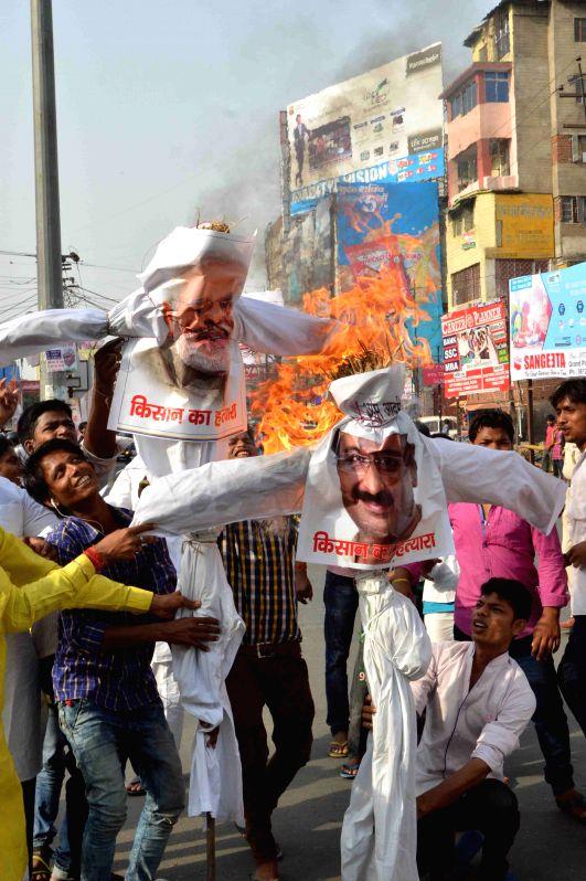 The members of Navnirman Morcha burn the effigies of Prime Minister Narendra Modi and Delhi Chief Minister Nitish Kumar during a demonstration in Patna on April 24, 2015. - Narendra Modi and Nitish Kumar