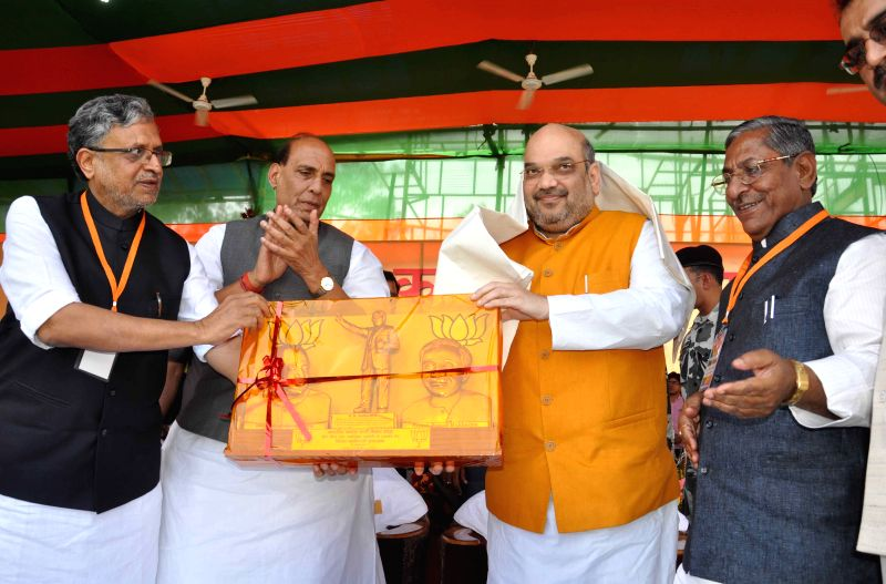 Union Home Minister and BJP leader Rajnath Singh and BJP chief Amit Shah with party leader Sushil Kumar Modi during a party worker's rally in Patna, on April 14, 2015. - Rajnath Singh, Amit Shah and Sushil Kumar Modi