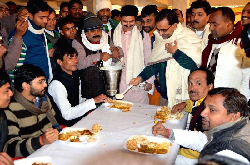 Union Minister of State for Human Resource Development Upendra Kushwaha serves food during a feast organised on Makar Sankranti in Patna, on Jan 14, 2015.
