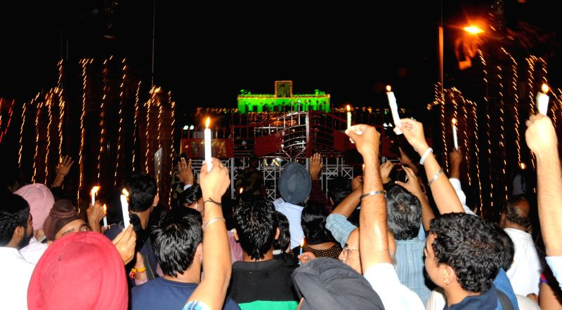 Peaceniks hold a midnight candlelight vigil near the border gates at Attari-Wagah joint check post to celebrate India's 68th Independence Day in Attari of Punjab's Amritsar district on Aug 15, 2014.