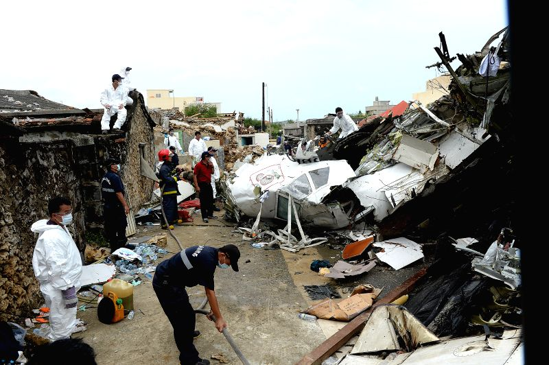 An investigator works at the accident site after a Taiwan plane smashed into residential buildings following a failed emergency landing in the outlying island county