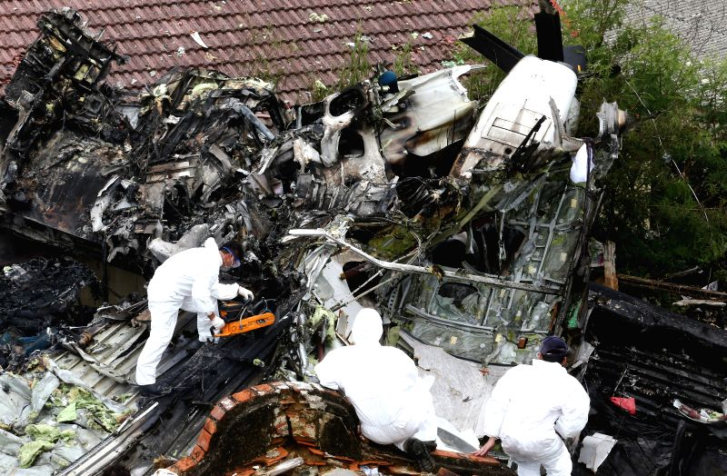 Investigators work at the accident site after a Taiwan plane  smashed into residential buildings following a failed emergency landing in the outlying island county ..