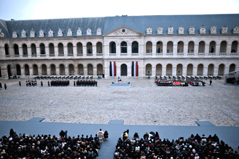 People attend a ceremony to pay tribute to the 130 people killed during the Nov. 13 terrorist attacks at the military museum Les Invalides in Paris, France, Nov. 27, ...