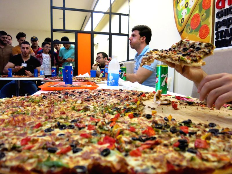 """People attend a contest to eat pizza in Baghdad, Iraq, Oct. 31, 2015. A contest to eat larger pieces of Pizza named """"Away from violence"""" was held in one of ..."""