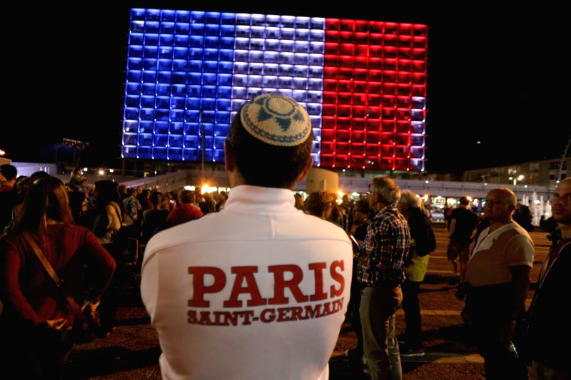 People attend a gathering to mourn for the victims of the Paris attacks in front of the Tel Aviv city hall, which is lit with the colors of the French national ... - Benjamin Netanyahu