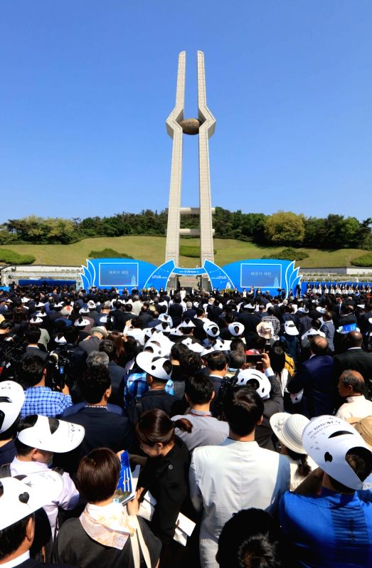 People attend an annual ceremony in front of the monument commemorating slain pro-democracy fighters at the Gwangju May 18 National Cemetery in the southwestern city of Gwangju on May 18, 2017, to ...