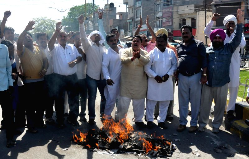 People burn effigy of Yoga guru Ramdev during a demonstration against his remark on Congress vice-president Rahul Gandhi in Amritsar on April 27, 2014. - Rahul Gandhi
