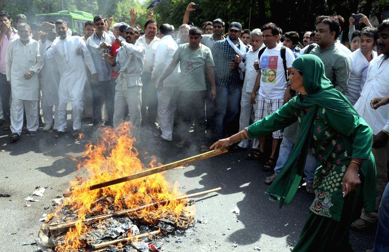 People burn effigy of Yoga guru Ramdev during a demonstration against his anti-dalit remark in New Delhi on April 27, 2014.